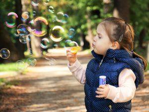 Kind spielt mit Seifenblasen