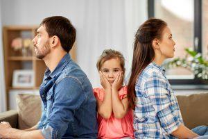 Kind sitzt zwischen Eltern, die sich den Rücken zuwenden